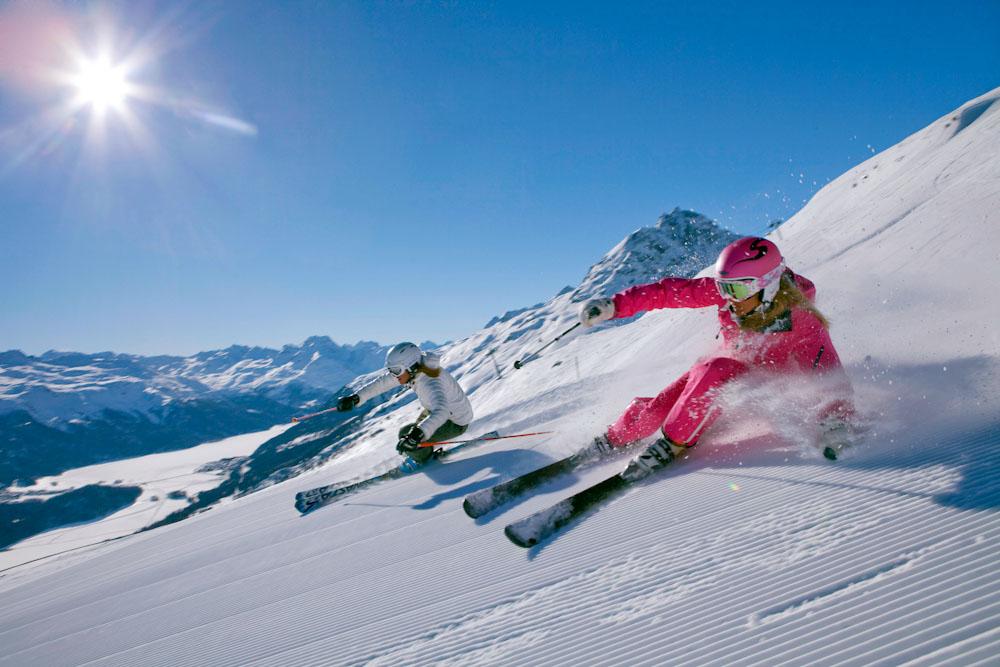 ENGADIN St. Moritz: Zwei Skifahrerin mit der Engadiner Bergwelt und den gefrorenen Engadiner Seen im Hintergrund